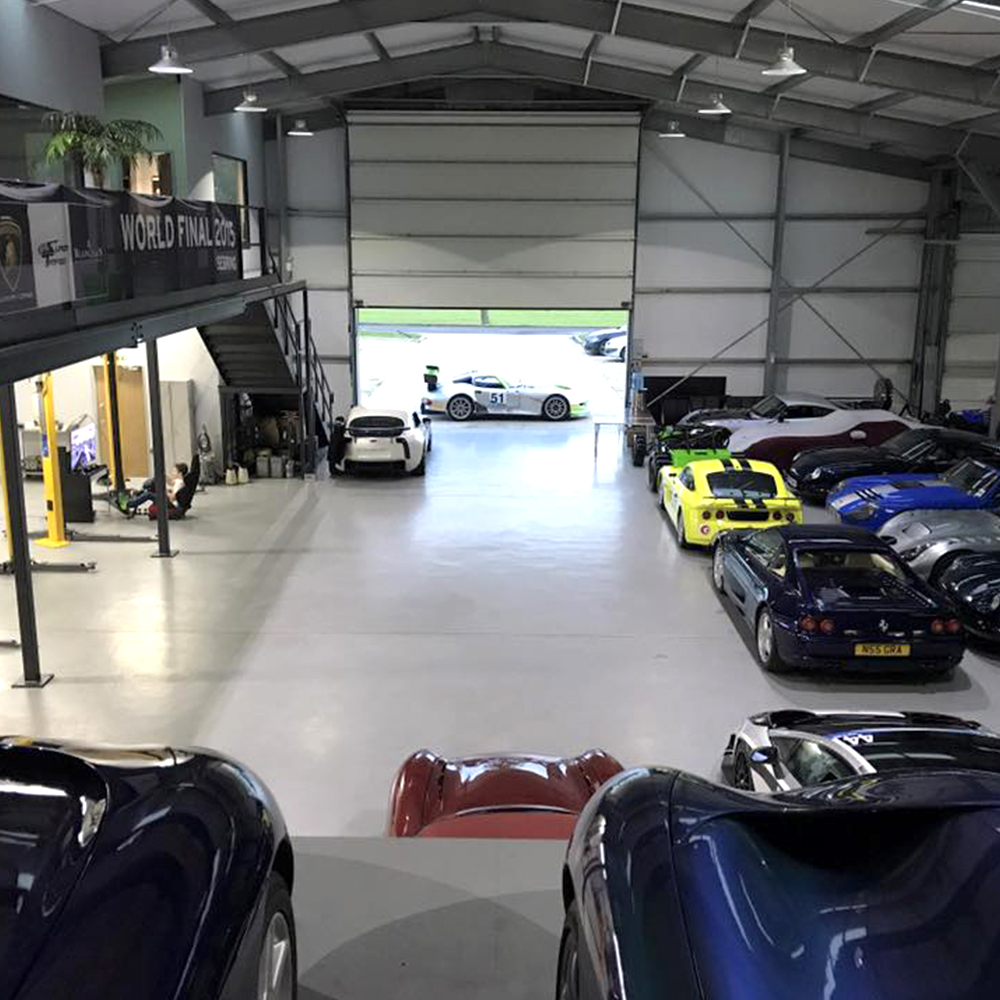 overview of topcats racing large workshop featuring numerous performance and road cars housed in workshop storage facility