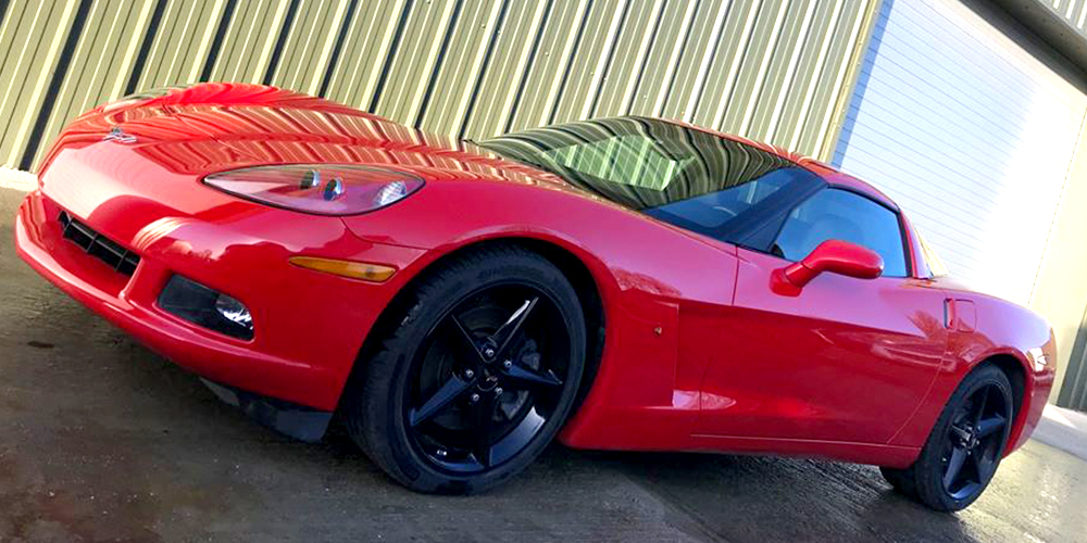 red chevrolette corvette c6 parked outside topcats racing workshop