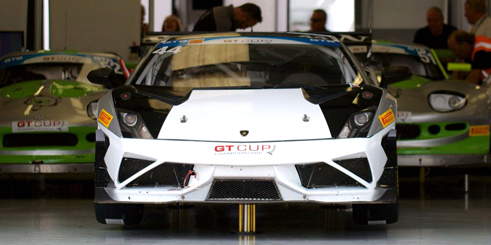white and black topcats racing lamborghini gallardo performance car in workshop