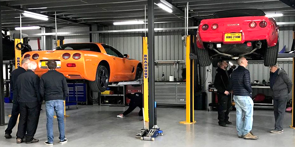 orange chevrolet corvette c6 and red corvette on ramp whilst topcats racing team discuss upgrades