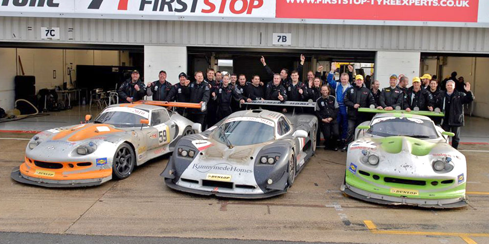 topcats racing team celebrating behind 2 marcos mantis cars and mosler mt900 at event