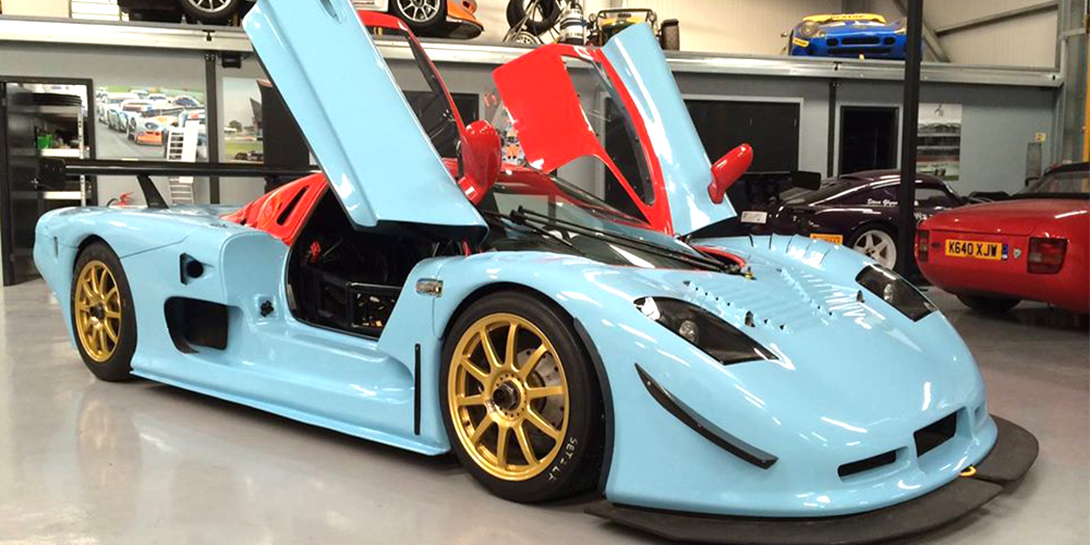 blue and red mosler mt900 with gullwing doors open on either side in topcats racing workshop