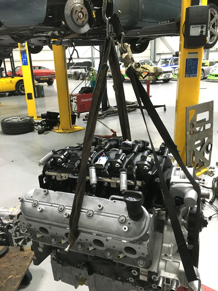v8 engine on hoist ready to go into vehicle at topcats racing workshop