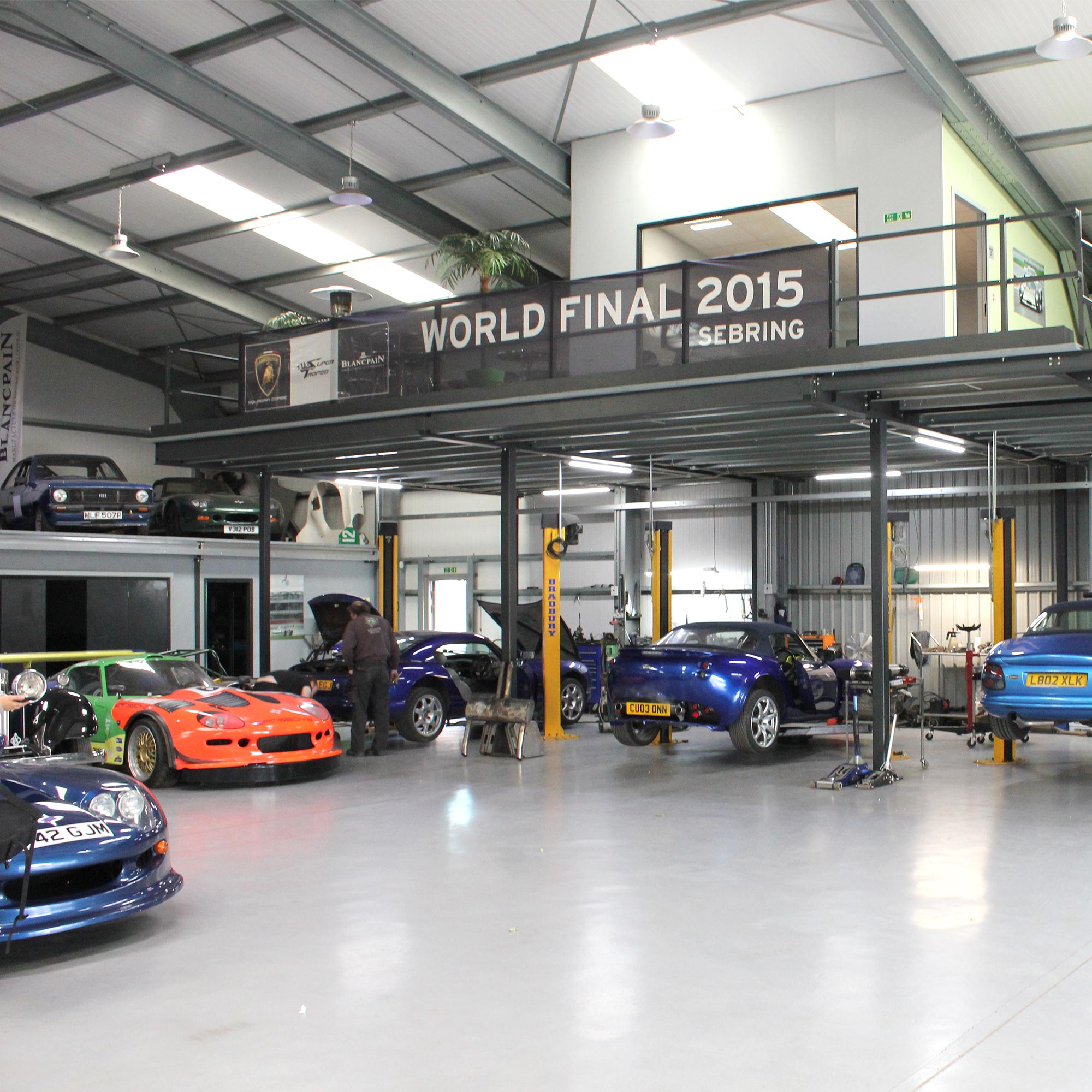 topcats racing workshop with variety of cars on ramp and overlooking balcony in distance