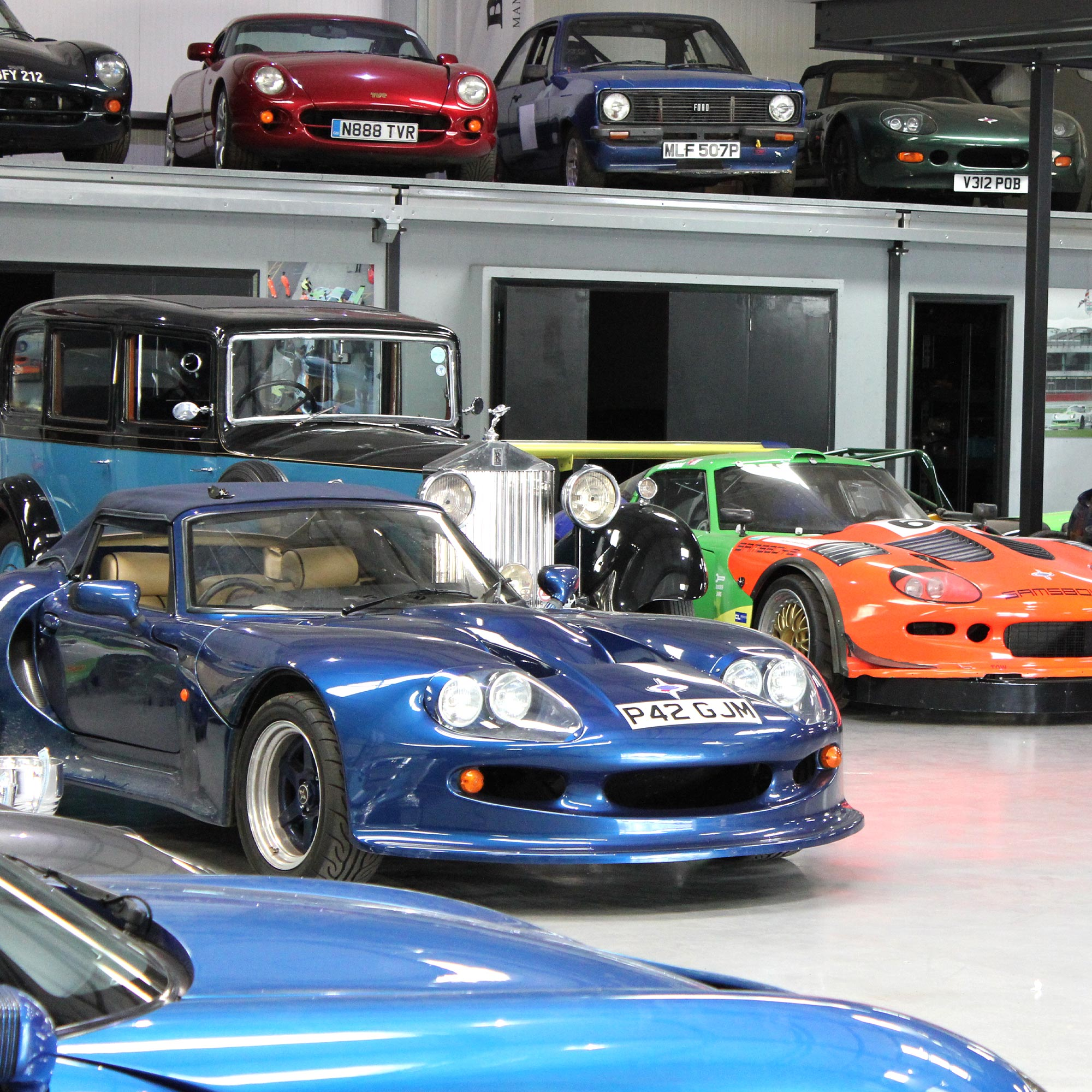 variety of performance and antique luxury cars housed at topcats racing workshop