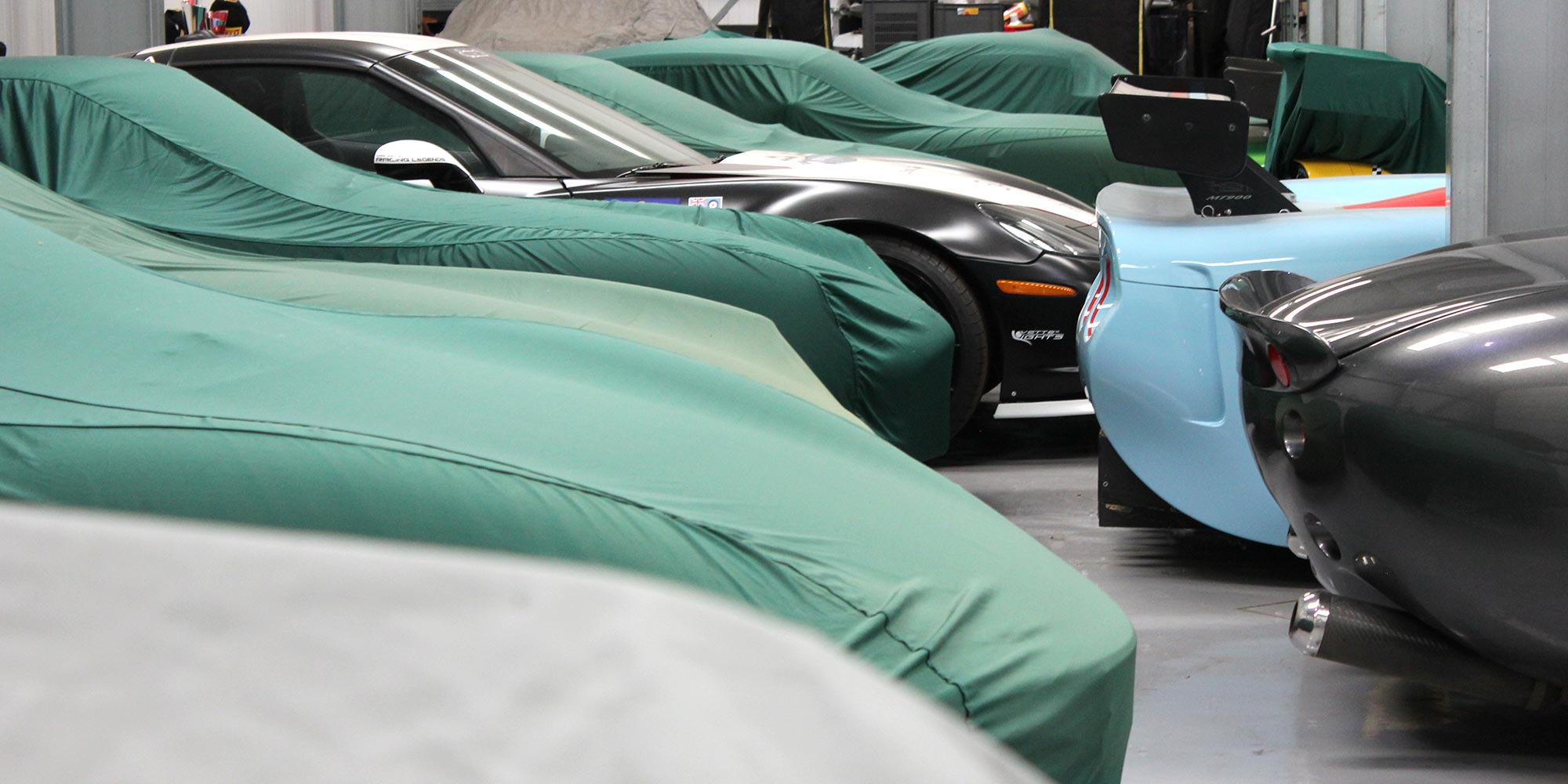 panoramic image of vehicles housed at topcats racing workshop safely stored with car covers