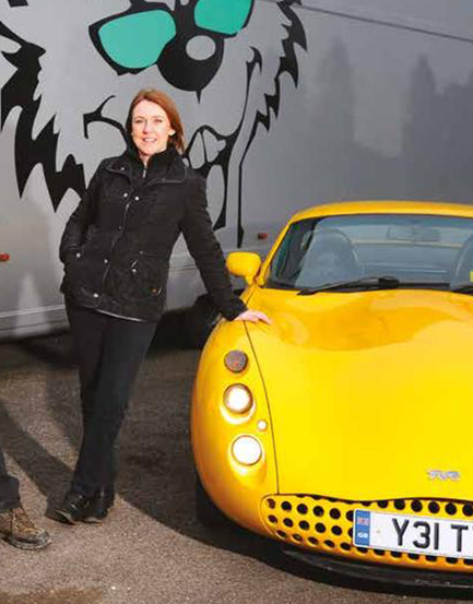 charlotte gilbert owner of topcats racing standing beside yellow tvr