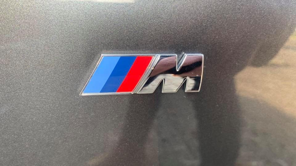 close up of BMW M225d M Sport (2014) emblem at topcats racing workshop