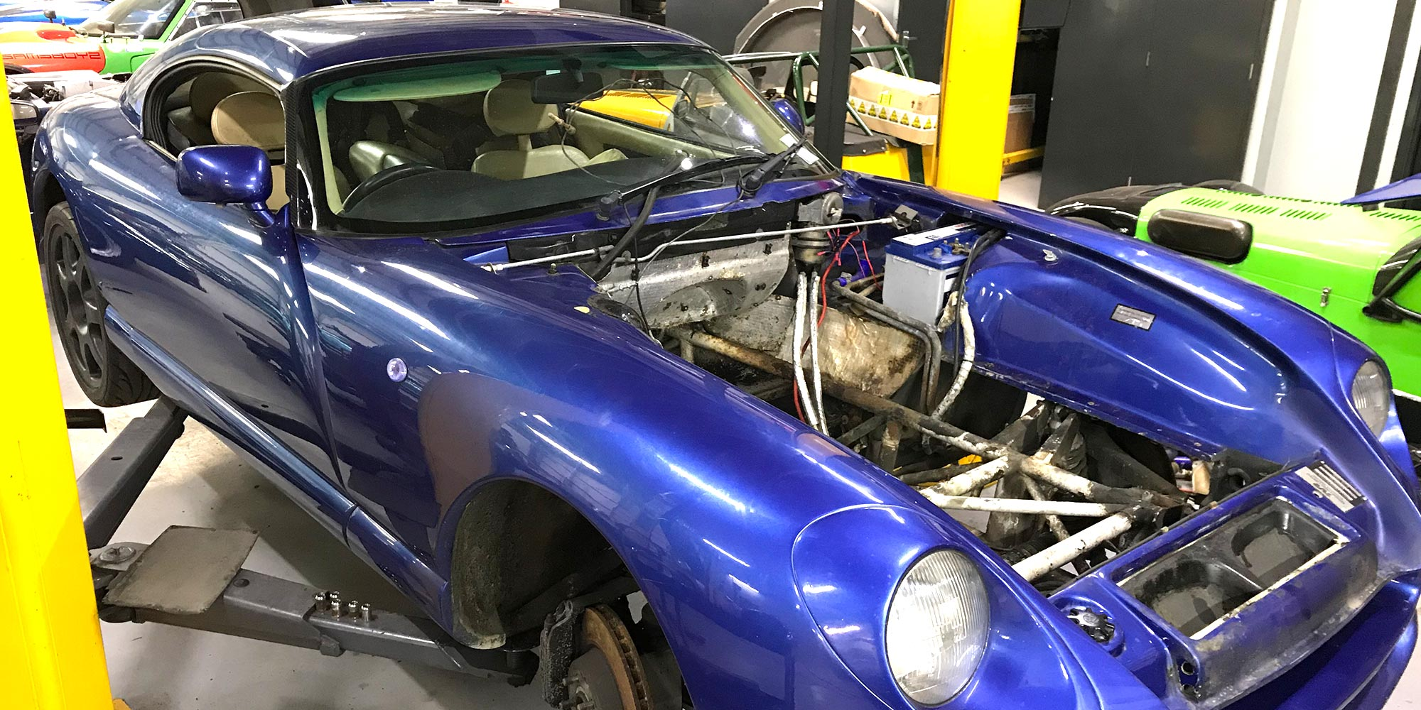 blue tvr cerbera with engine removed on ramp at topcats racing workshop